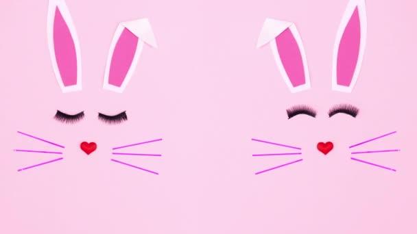 Zwei Osterhasen blinzeln mit Augenwimpern auf pastellrosa Hintergrund. Stop-Motion