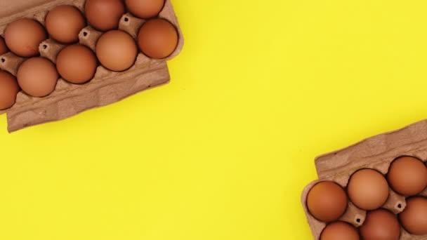 Frische Bio-Eier in Karton auf gelbem Hintergrund. Stop-Motion