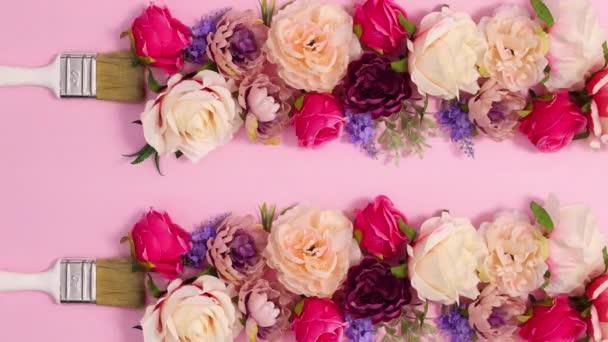 Pinsel passieren und lassen Blumenschmuck auf pastellrosa Hintergrund. Stop-Motion