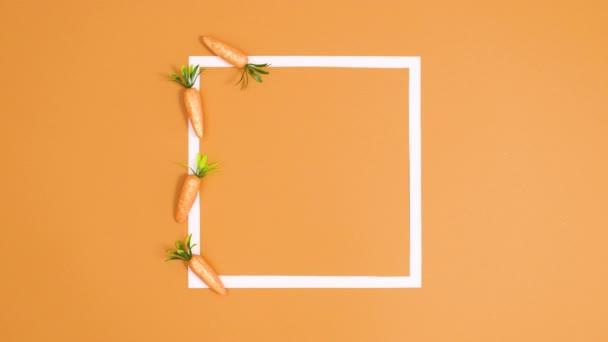 Glitzernde Möhren als Kopierrahmen für Ostern auf orangefarbenem Hintergrund. Stop-Motion