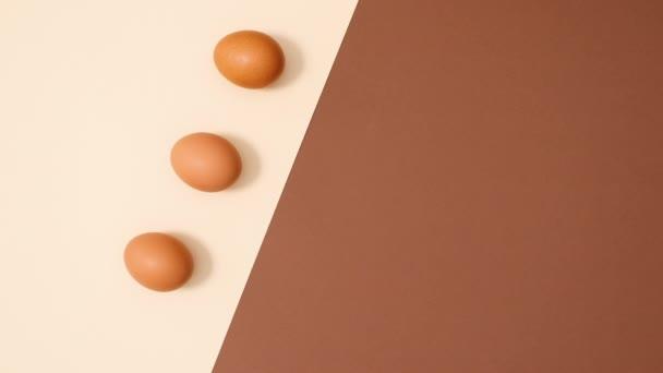 Flache Legemuster von Bio-Eiern erscheinen auf dunkelbraunem Hintergrund, Stop-Motion