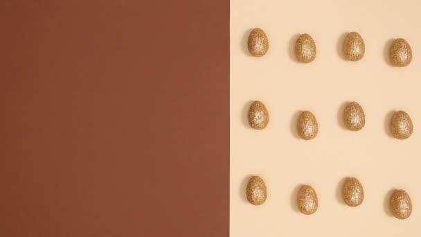 Ostermuster mit beweglichen goldenen Glitzereiern auf nudefarbenem Hintergrund. Stoppbewegungen flach legen