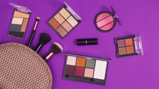 Make up products move in make up kit on purple background. Stop motion flat lay