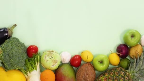 Čerstvé organické ovoce a zelenina tříděné pohybovat na dně světle zeleného pozadí. Zastavit pohyb ploché ležel zdravé jídlo