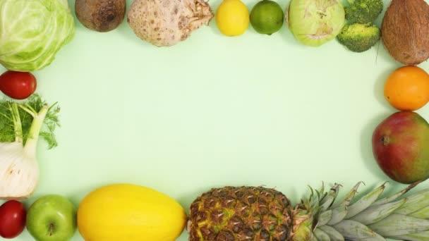 Čerstvé a zralé ovoce a zelenina tvoří kreativní rámec pro text na světle zeleném pozadí. Stop motion flat lay