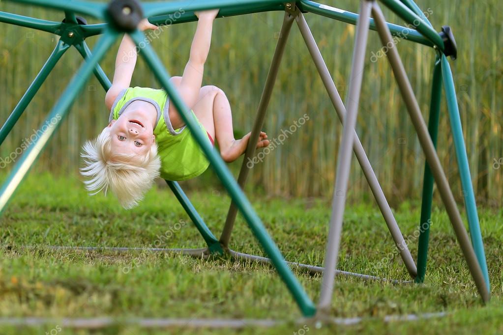 Klettergerüst English : Kleines kind spielen am spielplatz klettern klettergerüst