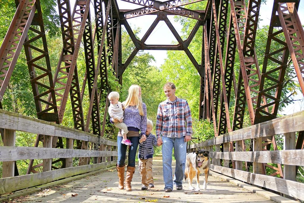Happy Family of Four People Walking Dog Outside on Bridge