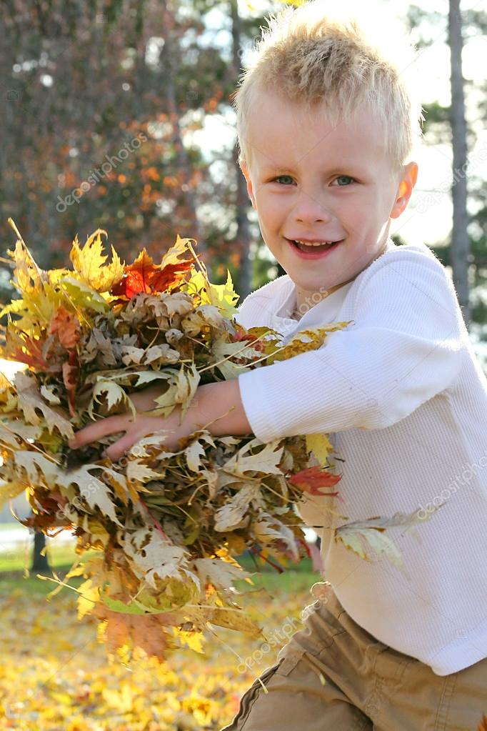 Young Child Running and Throwing Fall Leaves