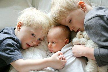 Big Brothers Hugging Newborn Baby Sister
