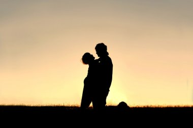 Silhouette of Child Laughing and Hugging Father at Sunset