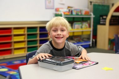 Young Child Sitting at Desk in Kindergarten CLassroom