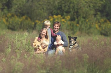 Happy Family of 5 People and Dog in Sunny Garden