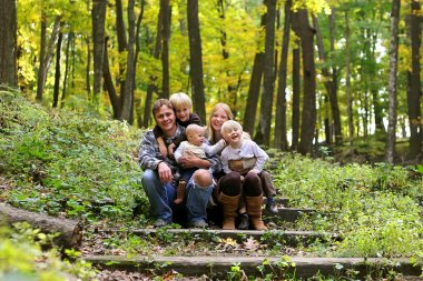 Happy Family of 5 people sitting in Autumn Forest