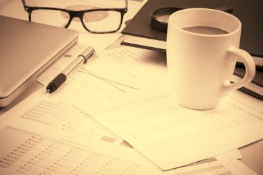 Business and financial report with coffee.Graph,book,glasses,Document is mockup