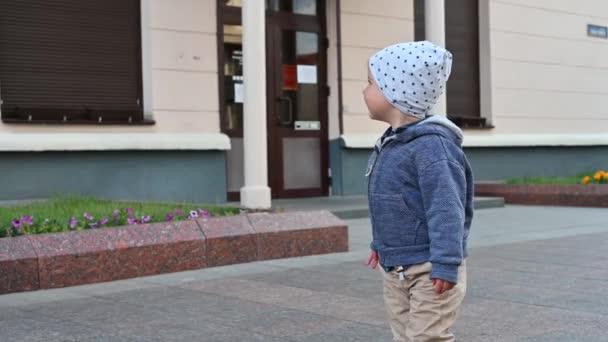 Közelkép egy gyerekről, aki a városban sétál.