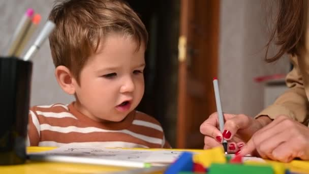 dítě maluje omalovánky s matkou. Zábavné vzdělávací hry