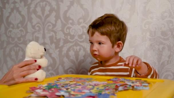 Anya és a baba plüssmacit játszanak. Szórakoztató játékok egy gyermekkel