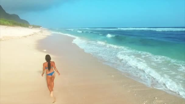 Young attractive woman enjoying relax while walking on sandy beach near ocean