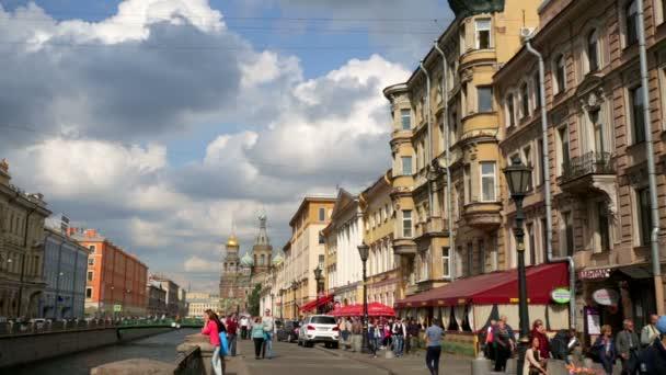 Turisté pěšky podél nábřeží ulice