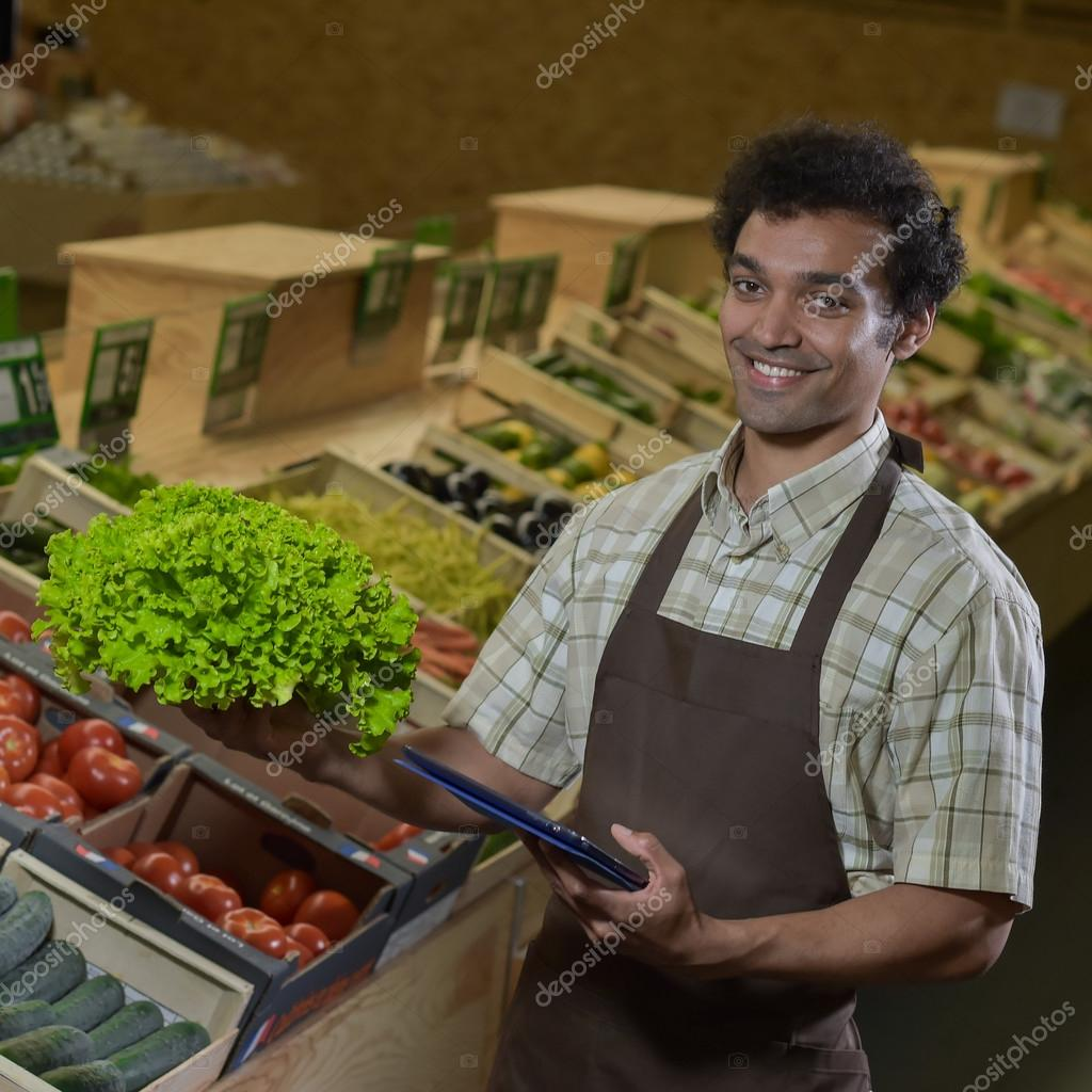 grocery store employee reading inventory list on digital tablet