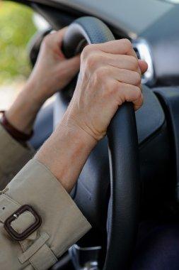 Senior woman hand on steering wheel
