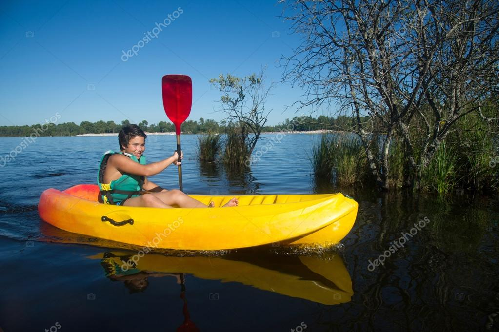 Teen making canoe kayak on a lake