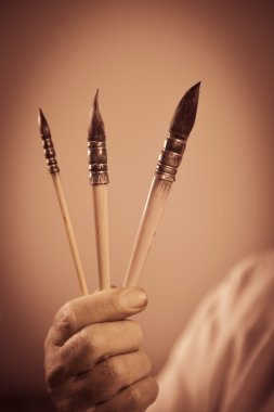Painter's hand holding three paintbrushes
