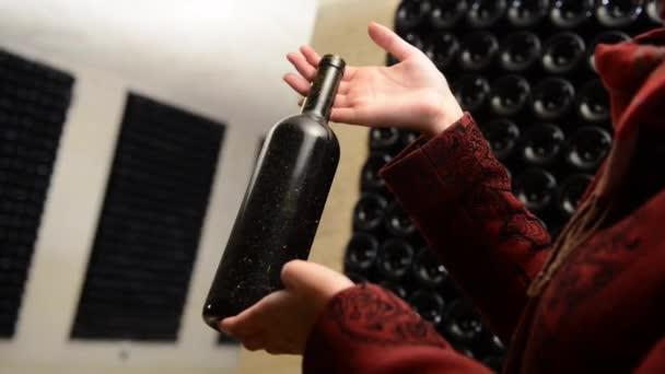 A women holds a bottle of wine in an aging cellar.Bordeaux Wineyard