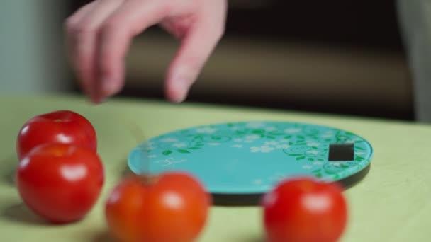 Mann wiegt frische Tomaten auf einer Küchenwaage, Nahaufnahme