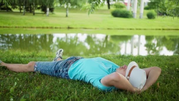 Muž v bílém klobouku odpočívá na jezeře ve veřejném parku