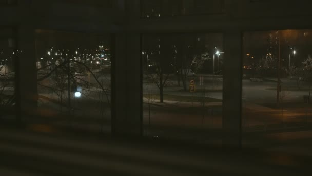 Noční opuštěná ulice, výhled z okna skrz žaluzie, sledování kamer