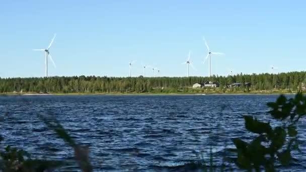 Velké větrné turbíny s lopatkami na poli u moře. Větrný park modrá obloha s dřevěnými chatami. Životní prostředí šetrné krajiny čisté energie. Alternativní větrná zelená energie.