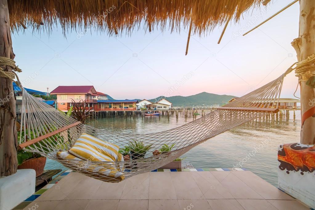 terrace with hammocks in tropical beach at sunrise