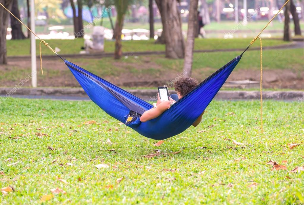 man lying on hammock in garden with tablet computer.