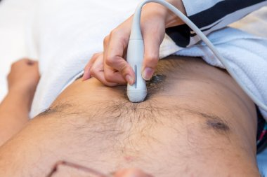 Closeup of man getting an ultrasound scan on abdominal by doctor