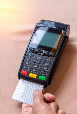Hand Swiping Credit Card on POS terminal in Store