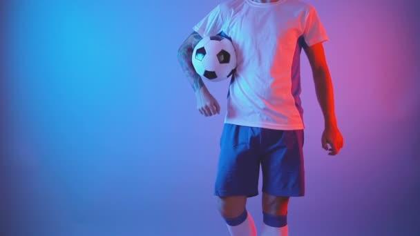 Nerozpoznatelný fotbalista pózující s míčem uvnitř, izolovaný záběr