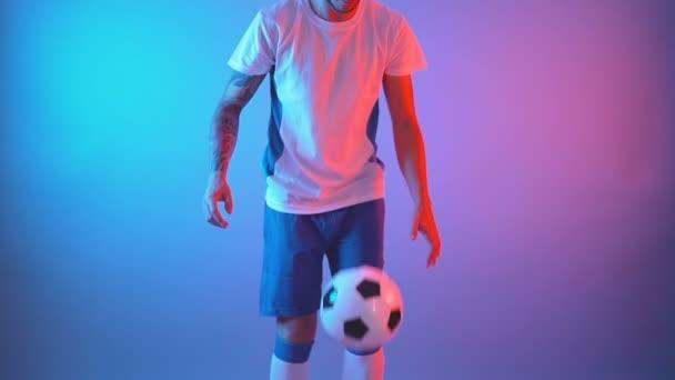 Profil pohled profesionálního fotbalisty v týmové uniformě žonglování míč s nohama, zpomalení