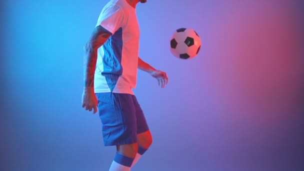 Male soccer football player juggling ball on legs in studio