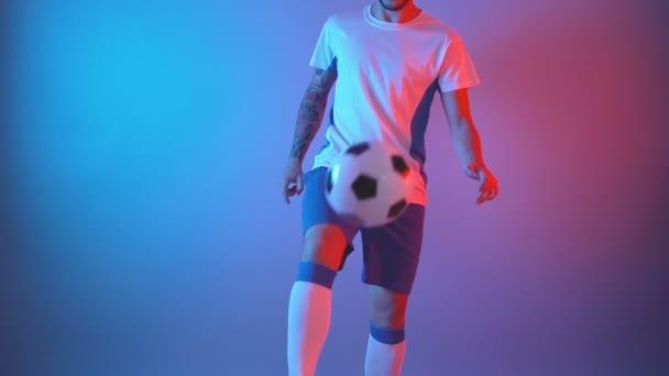 Profesionální fotbalista žonglování míč s nohama a koleny
