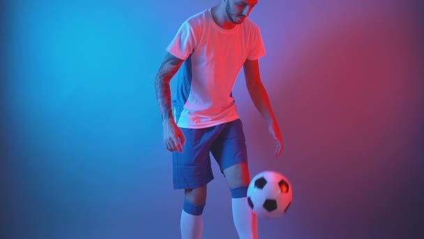 Professional football player warming up doing juggling with legs. Slow motion, front view