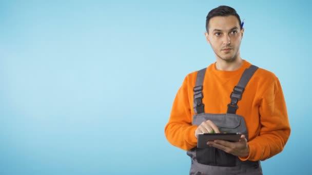 Opravář pracuje na tabletu proti světle modrému pozadí