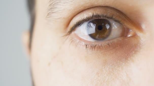Nahaufnahme eines jungen Mannes, der das rechte Auge schließt und blinkt