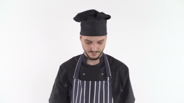 Seriöser Koch in Uniform geht in die Kamera, vor weißem Hintergrund