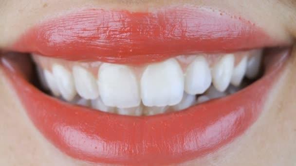 Weibliche Lippen mit rotem Lippenstift lächeln und zeigen perfekt weiße Zähne. Nahaufnahme