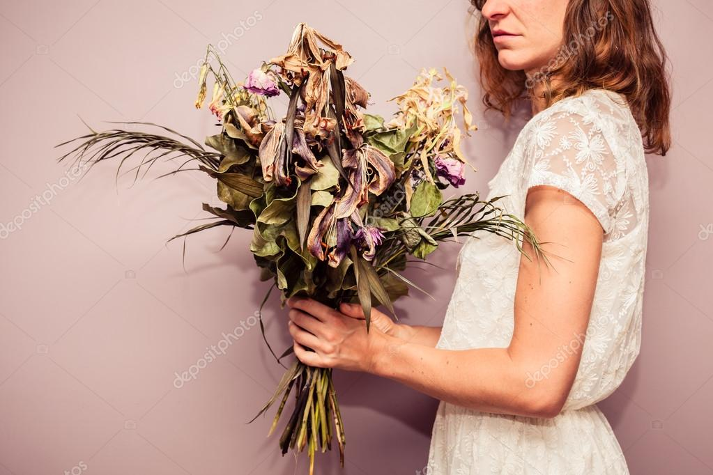 Young woman holding bouquet of dead flowers — Stock Photo © lofilolo ...