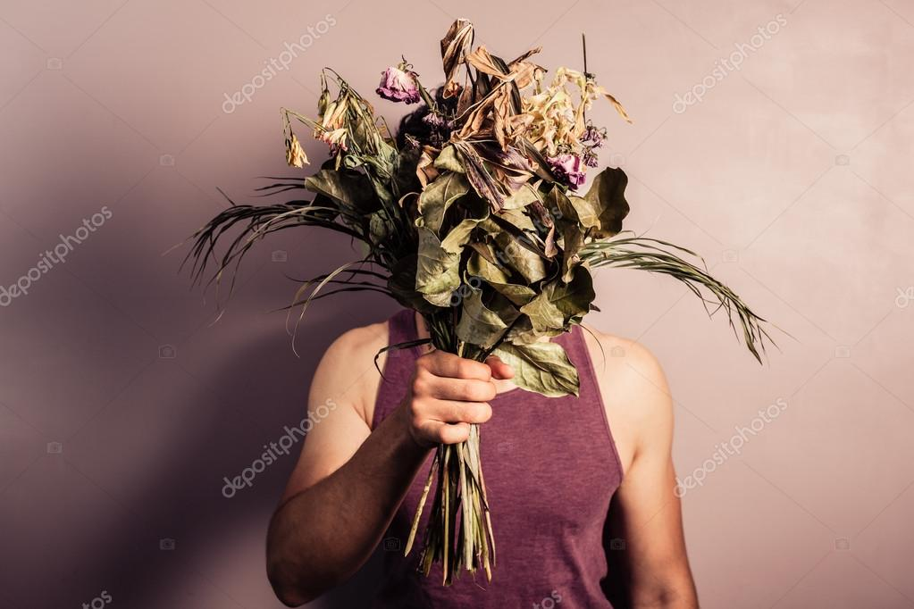 Young man holding bouquet of dead flowers — Stock Photo © lofilolo ...