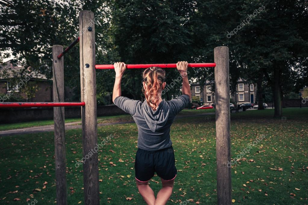 A young woman is doing pullups in the park
