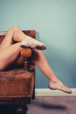 Woman in ballet slippers on sofa