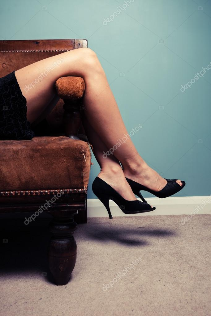 804982c2 Młodą kobietę sexy wysokie obcasy i sukienka leży na kanapie — Zdjęcie od  ...